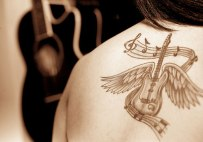 grey-ink-winged-guitar-tattoo-on-back
